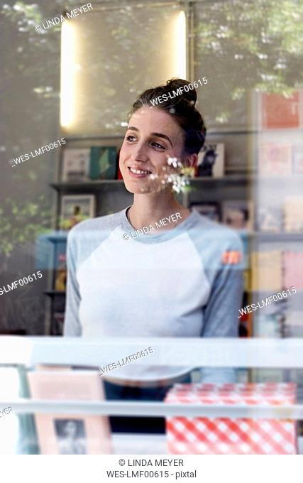 Portrait of smiling young woman in a bookshop looking through window