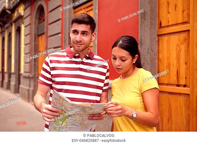 Young couple studying a map and looking right while smiling happily and dressed casually in t-shirts with old buildings behind them