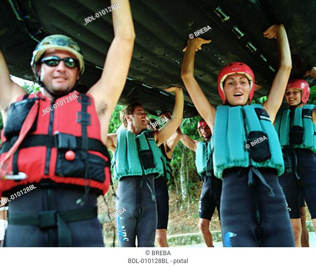 group of young people getting ready for river rafting