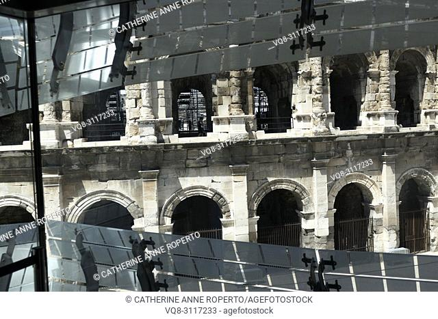 The segmented, geometric light reflectors on the Roman Museum facade part to reveal the arcading of the Amphitheatre at Nimes