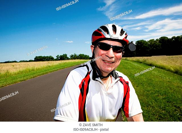 Senior man riding bicycle through countryside