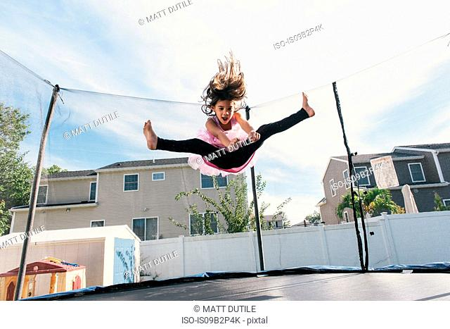 Girl in mid air jumping on trampoline