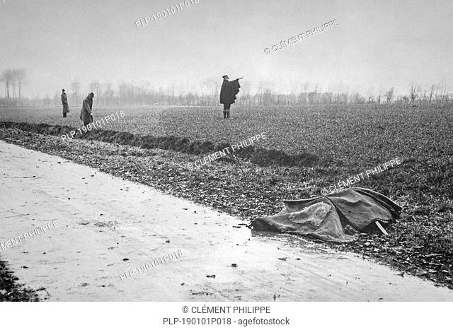 Mid twentieth century black and white photo showing murdered victim covered with cloth and gendarme and police inspectors inspecting field and ditch