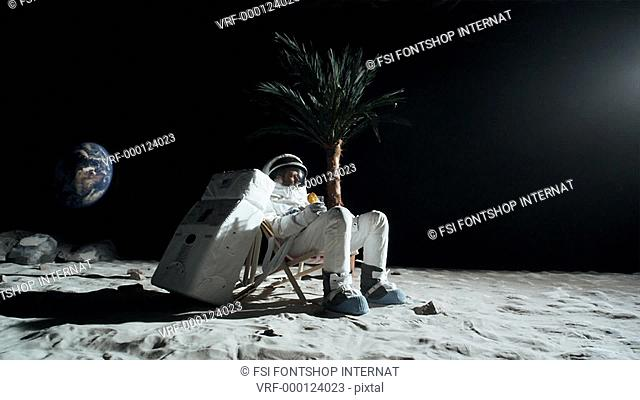 SLO MO, WS two astronauts relaxing on the moon