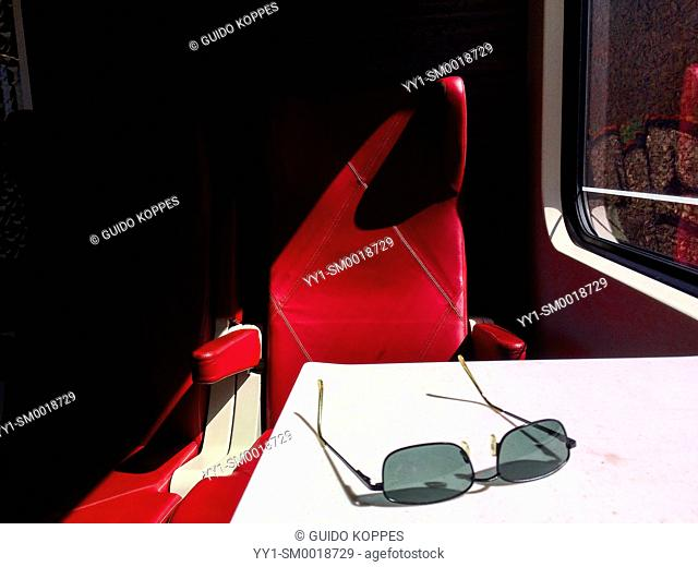 Intercity train, Breda, Netherlands. Sunglasses on a side table of the train's first class during a commute in sunny weather