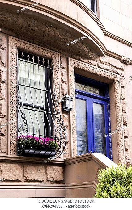 New York City, Manhattan, Upper West Side. Close up of Brownstone Townhouse Entry and Burglar Bar Window with Flower Holder