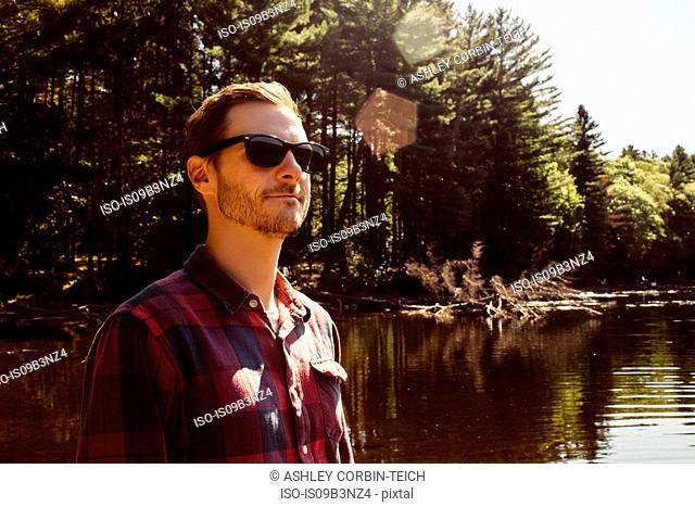 Man beside lake, looking at view