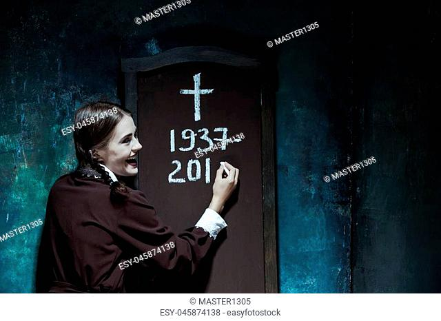 Halloween theme: Portrait of a young smiling girl in school uniform as killer woman against school board
