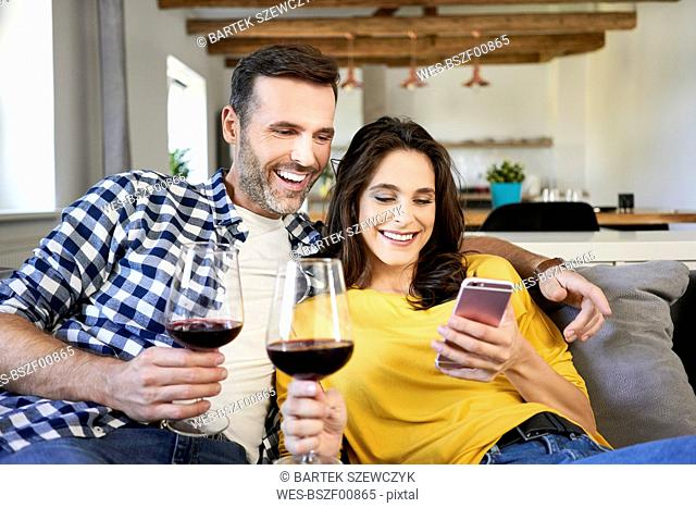 Couple sitting in living room, drinking red wine, using smartphone