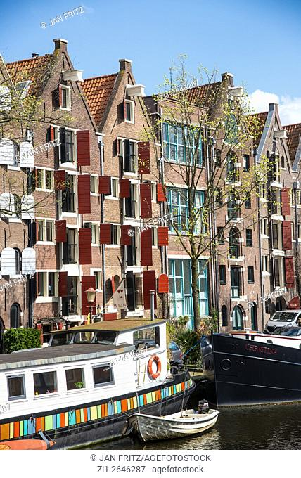 old historic buildings and houseboat at amsterdam holland