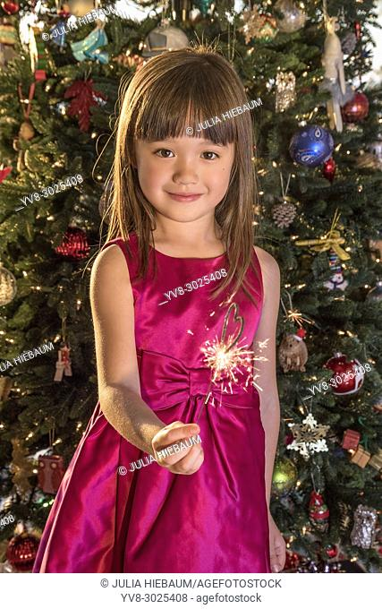 Five year old girl holding a heart shaped sparkler at Christmas Eve