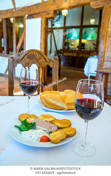 Spanish appetizer: two glasses of red wine and tapa of pate and sliced bread in a typical restaurant. Navalcarnero, Madrid province, Spain