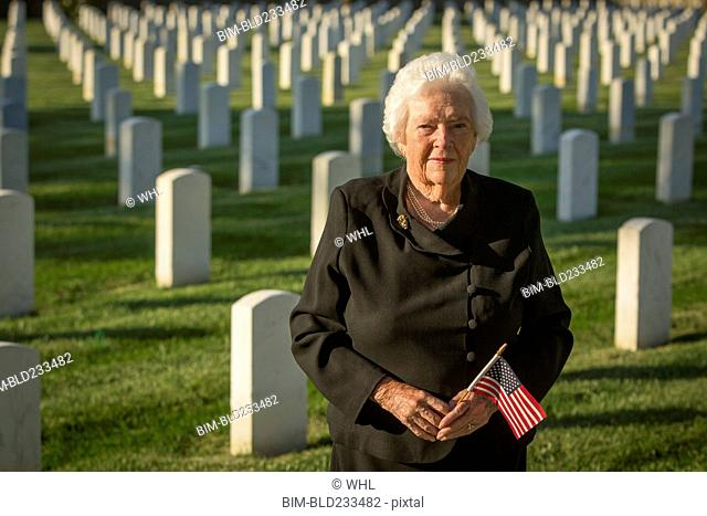 Caucasian widow holding American flag in cemetery