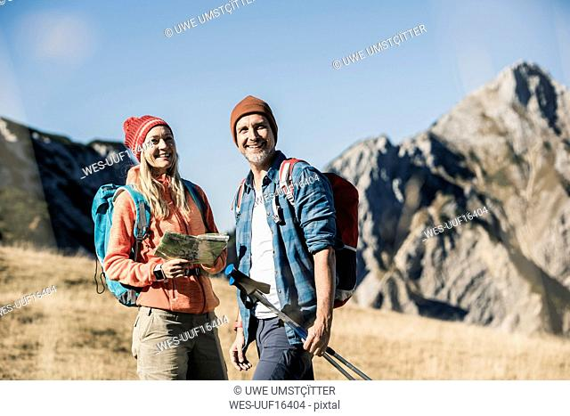 Austria, Tyrol, happy couple with map on a hiking trip in the mountains