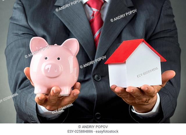 Midsection of businessman holding piggy bank and house model