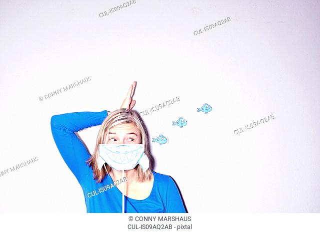 Studio shot of young woman with hand on head holding up drawing of sharks mouth