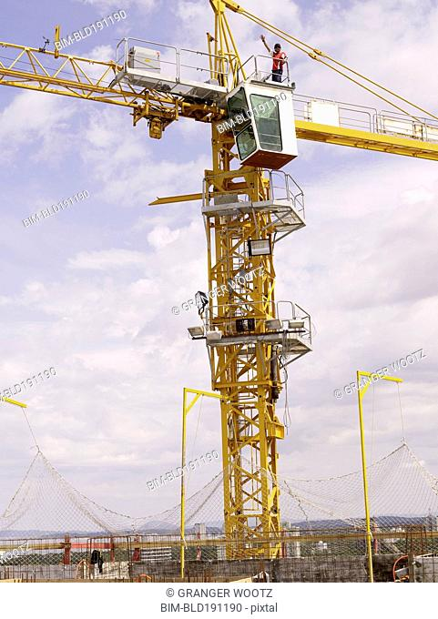 Construction worker on top of crane