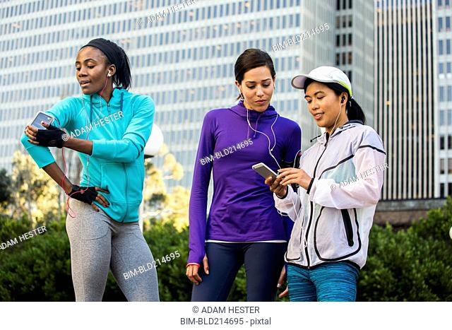 Runners using cell phone near high rise buildings