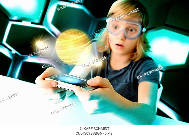 Boy with hand held computer staring at digital spinning planet