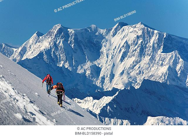 Caucasian hikers climbing snowy mountain, Monte Rosa, Piedmont, Italy