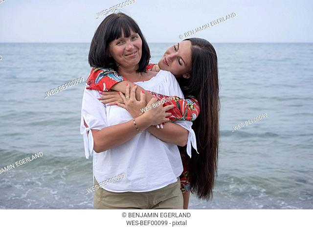Greece, portrait of happy mother with her adult daughter in front of the sea