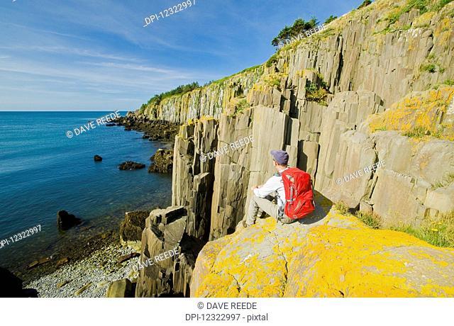 Hiker along basalt rock cliffs, Bay of Fundy; Brier Island, Nova Scotia, Canada