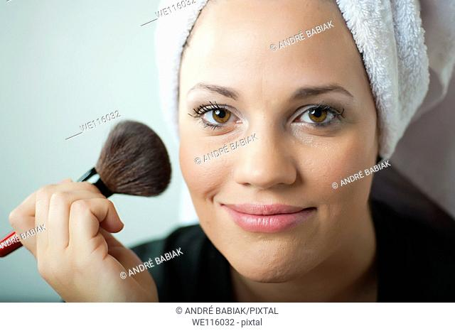 Attractive woman using brush putting on makeup powder