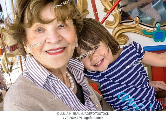 Toddler girl with her great-grandmother at the merry-go-round, San Diego, California