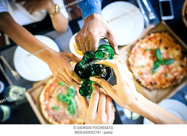 Group of friends having pizza and beer at home