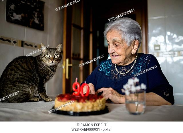 Senior woman celebrating ninetieth birthday with her cat