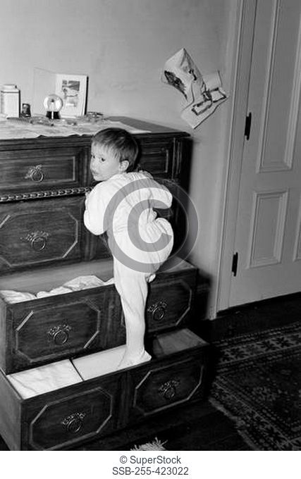 Girl playing on drawer chest