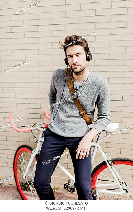 Portrait of young man with racing cycle and headphones