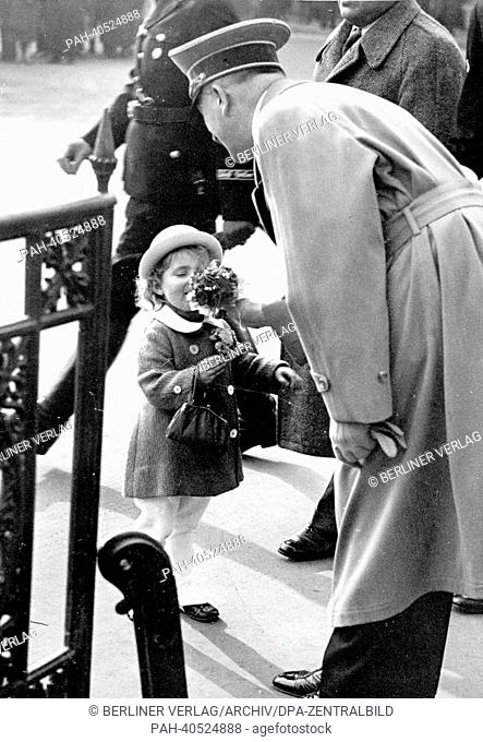 The image from the Nazi Propaganda! shows Adolf Hitler receiving flowers from a little girl on his way to a reception at the Ministry of Public Enlightenment...