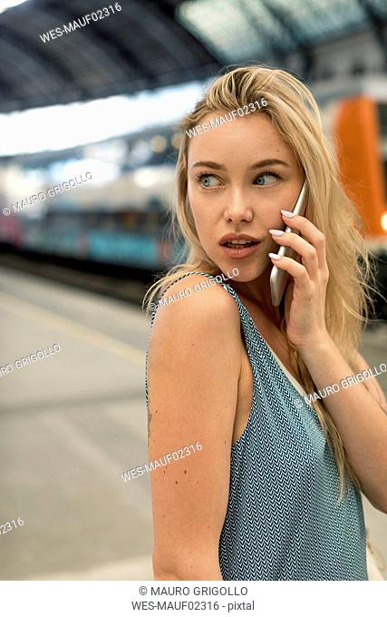 Portrait of young woman on cell phone at the train station looking around