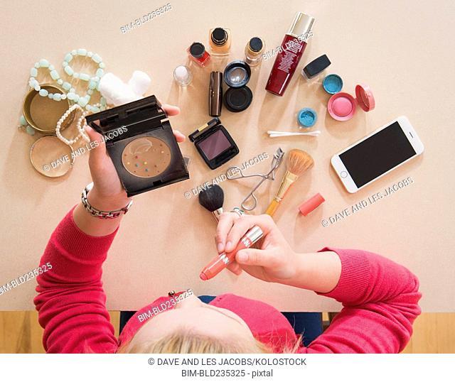 Caucasian woman applying makeup at table