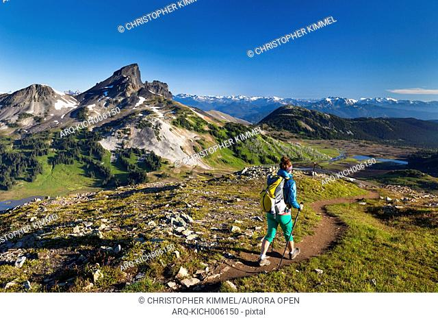 A young woman backpacking on the Panorama Ridge Trail with Black Tusk Mountain in the background in Garibaldi Provincial Park, British Columbia, Canada