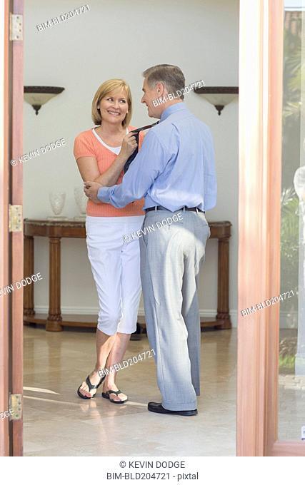 Caucasian couple talking in hallway