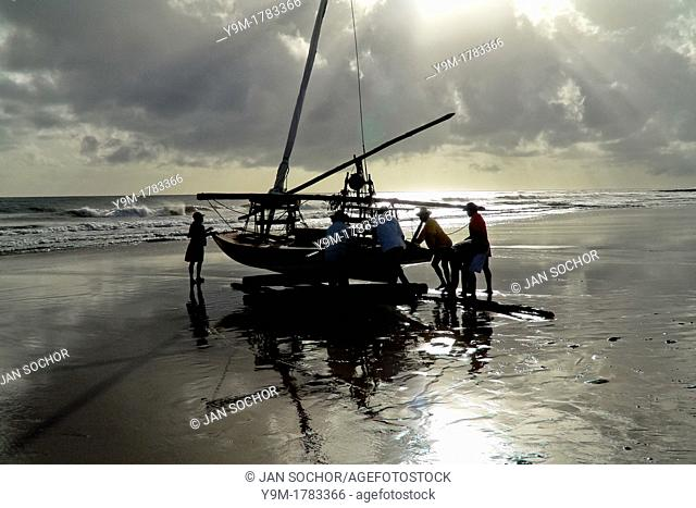 Brazilian fishermen pushing their boat manually towards the ocean during the sunrise in Uruau, state Ceara, Brazil, 16 March 2004  Fishermen use a unique wooden...