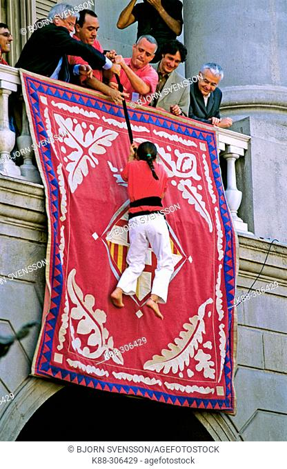 A young 'Castellera' (member of a human tower) climbs up to the mayor of Barcelona, who is on the City Hall balcony. Plaça de Sant Jaume. Barcelona
