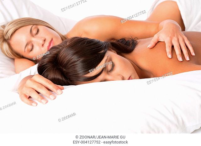 Blond woman and brunette lying down in white bed