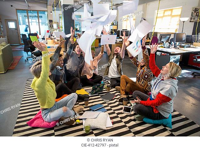 Playful, enthusiastic creative business team throwing paperwork overhead in open plan office