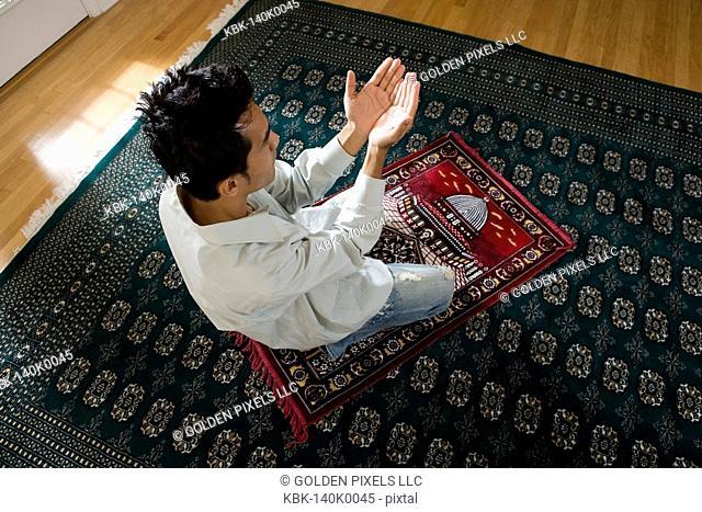 A Muslim man praying on a prayer mat