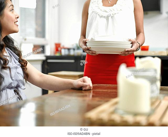 Two young women preparing for meal in kitchen