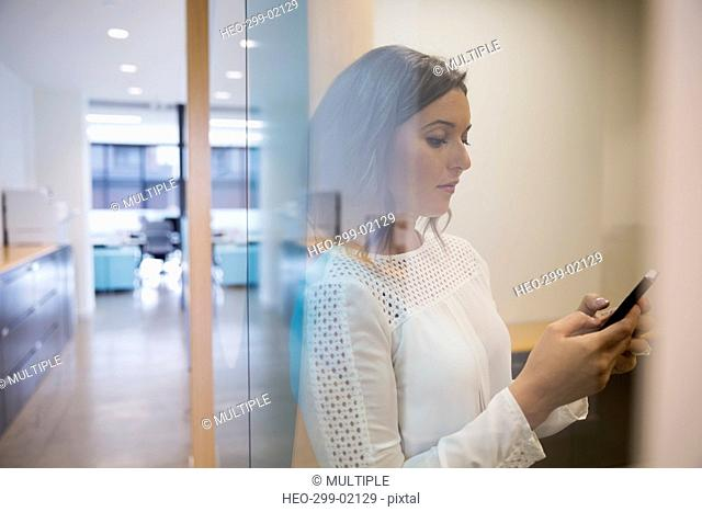Businesswoman texting with cell phone in office