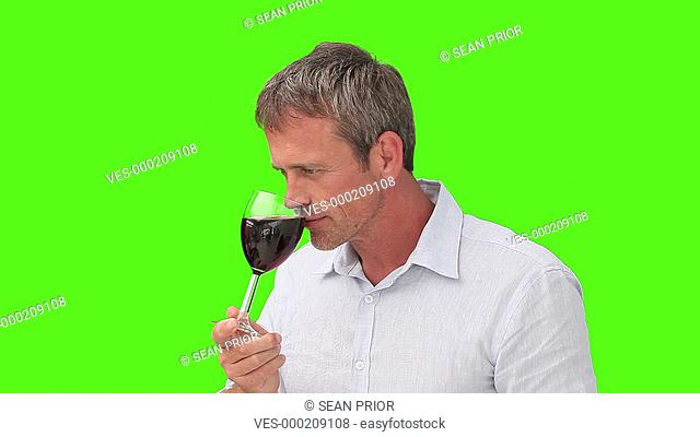 Ein Mann trinkt Wein. Er steht vor einem Green-Screen
