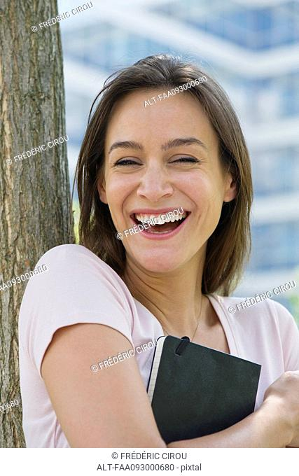 Woman holding book, laughing, portrait