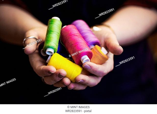 Woman holding hands out full of bobbins of embroidery silks in bright colours