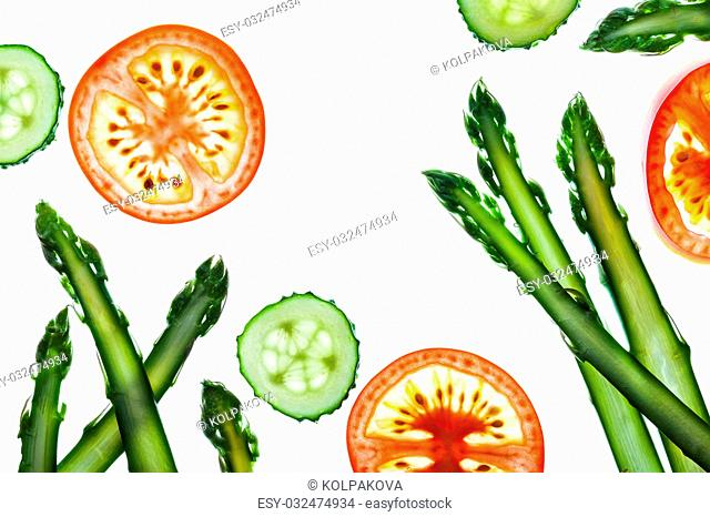 Thin slices of fresh vegetables on a white background