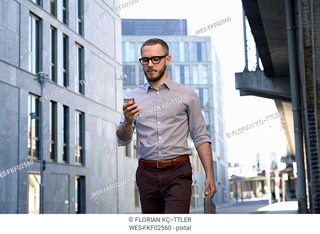 Businessman looking at cell phone in the city