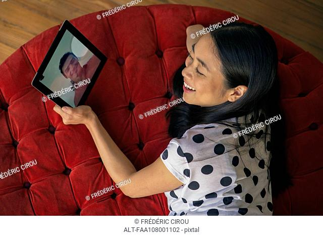 Woman video conferencing with boyfriend on digital tablet